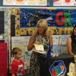 AJ is presented his certificate and awards by Mrs. Ramirez.