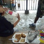 AJ eating some stew on a bus bench in Belize City.