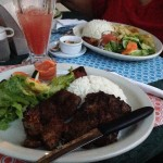 In the front is pepper steak, then fresh watermelon juice, and in the back is coconut sauce fish.