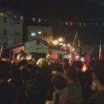 The torch runners going through the crowd to the police station.